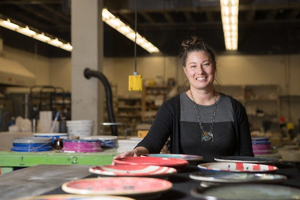 Melody Shipley stands with plates made as part of her art therapy project.
