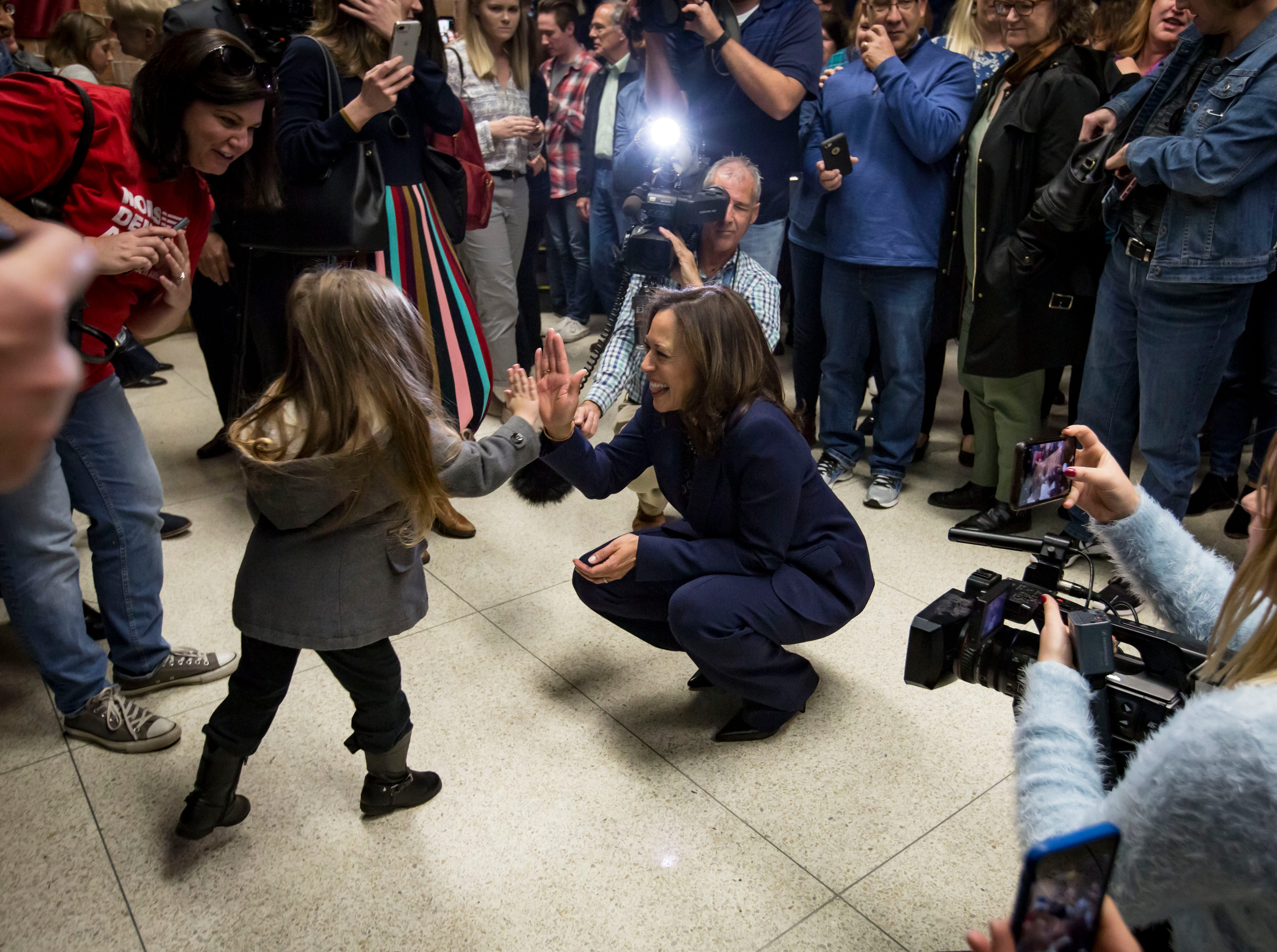 Democratic Senator Kamala Harris of California high fives Jessica Mayland, 3, of Maxwell after a DMACC Early Vote rally  Monday, Oct. 22, 2018, in Ankeny, Iowa. She appeared with Congressional candidate Cindy Axne, State Senate candidate Amber Gustafson and Iowa House candidate Heather Maston.