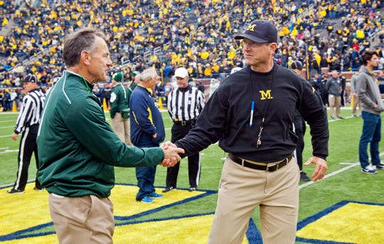 Michigan State head coach Mark Dantonio shakes hands with Michigan head coach Jim Harbaugh on the Michigan Stadium field before the game Oct. 17, 2015.
