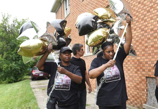 Starleigh Cleveland  (from right) and Aufelia Palmer, mother of Antonio Walker, prepare to release balloons in remembrance of Antonio Walker, who was killed July 12, 2011, as family gathered in Detroit on Saturday, July 21, 2018.