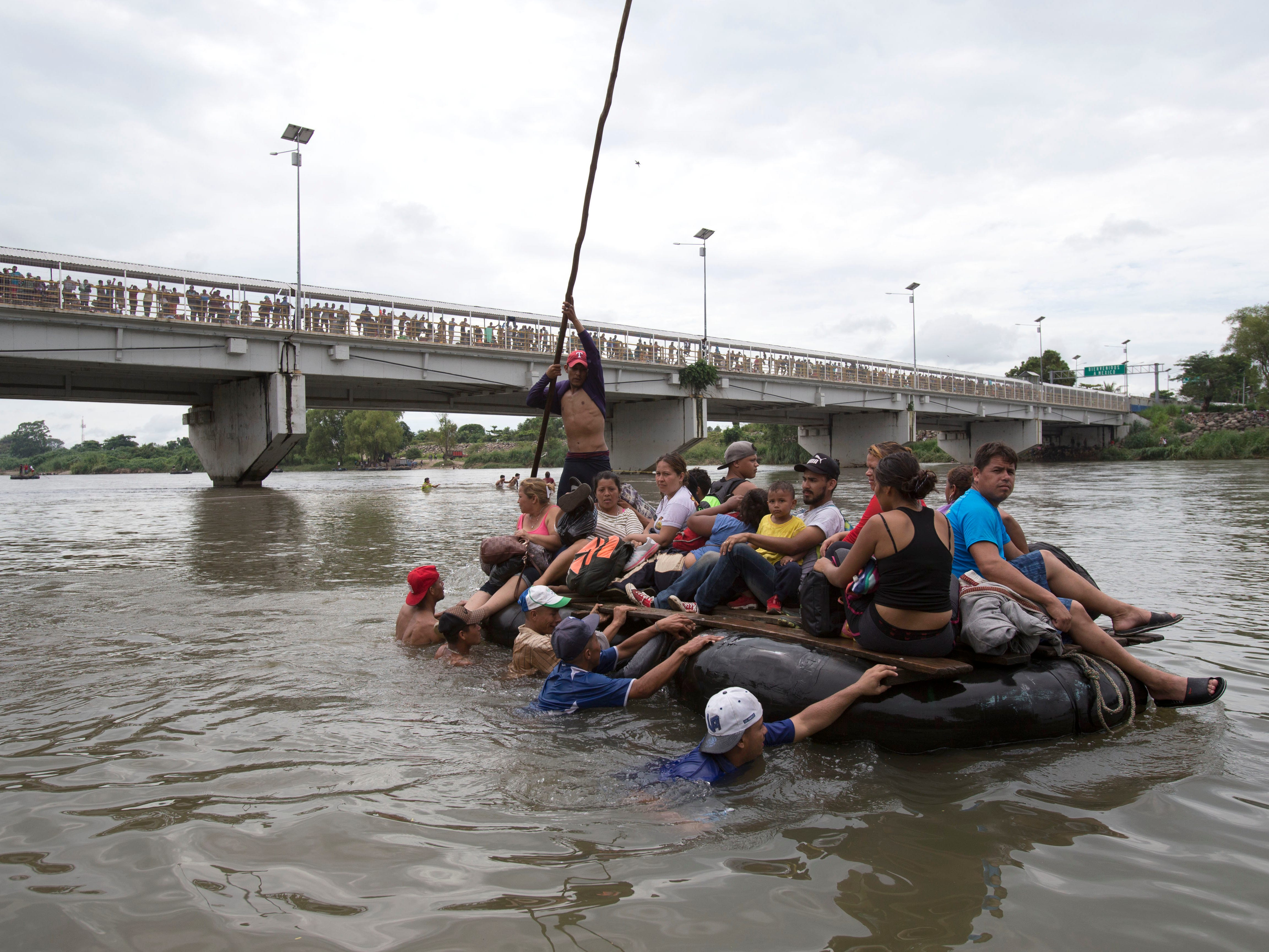 A group of Central American migrants cross the Suchiate River aboard a raft made out of tractor inner tubes and wooden planks, on the the border between Guatemala and Mexico, in Ciudad Hidalgo, Mexico, Saturday, Oct. 20, 2018. After Mexican authorities slowed access through the border bridge to a crawl, hundreds of migrants are boarding the rafts or wading across the river and crossing into Mexico illegally.