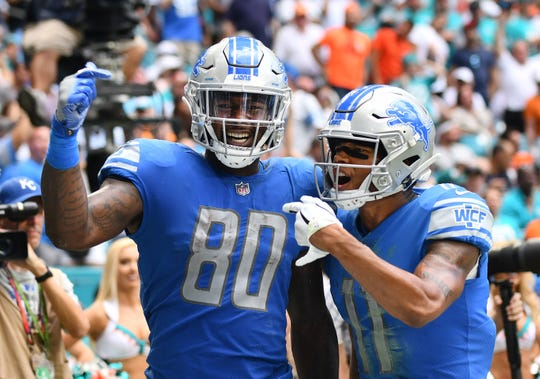 Lions tight end Michael Roberts (80) celebrates with Marvin Jones Jr. after his second touchdown Sunday against the Dolphins.
