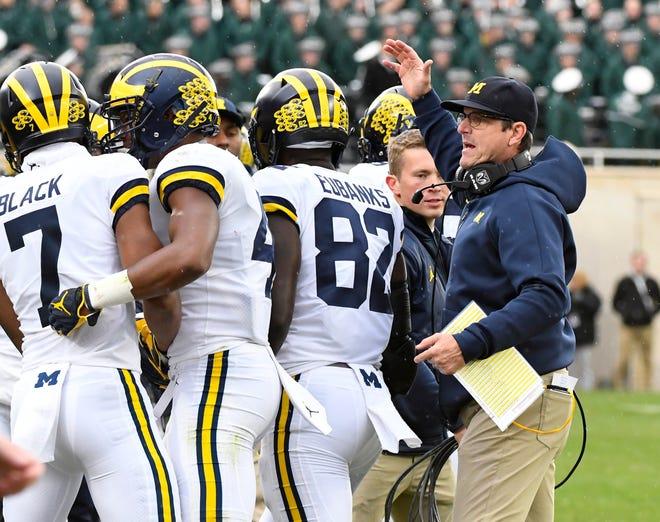Jim Harbaugh congratulates his team after a third-quarter touchdown against Michigan State.