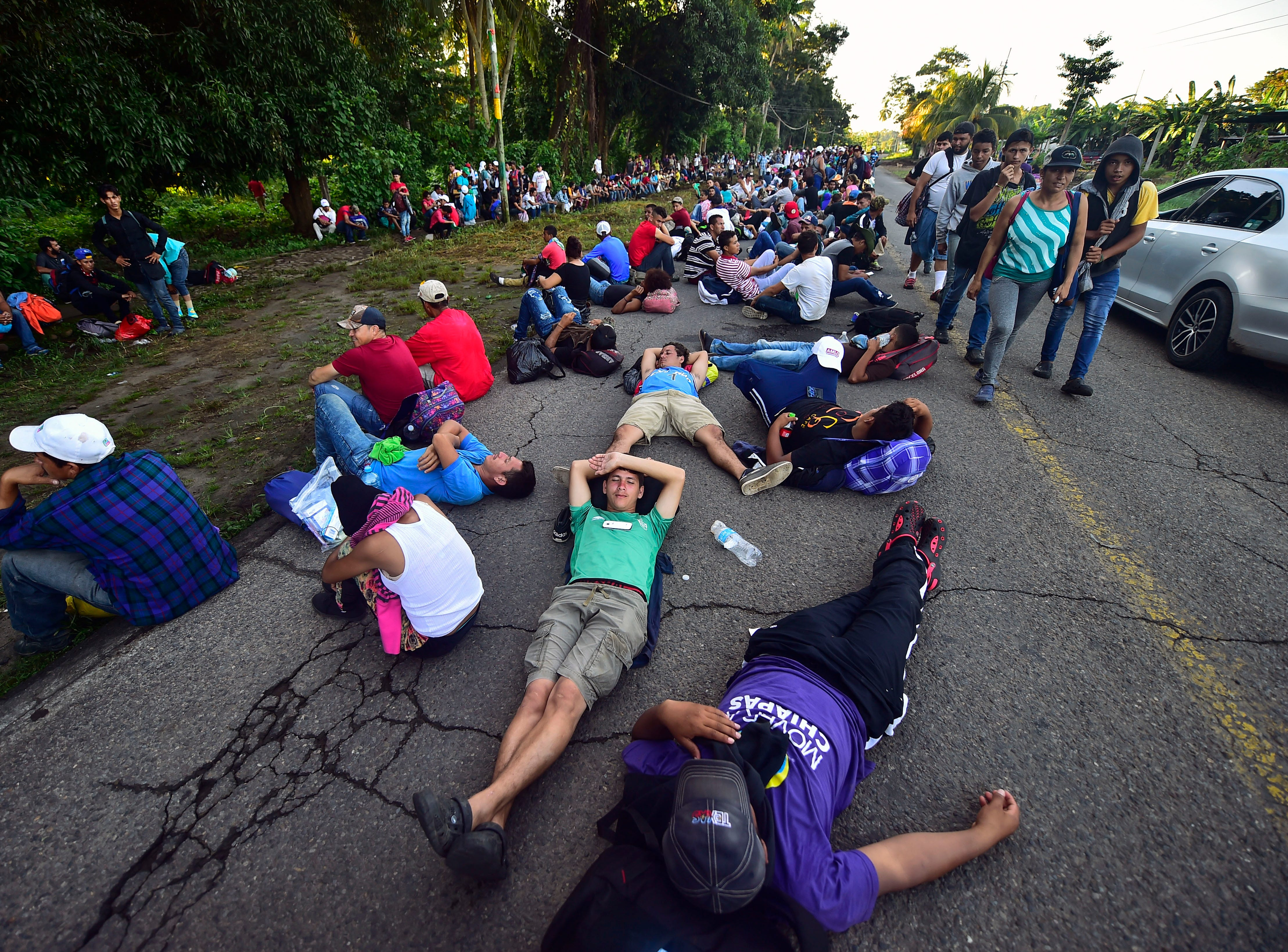 Honduran migrants heading in a caravan to the US, rest alongside the route, in Metapa, Chiapas state, Mexico on October 22, 2018. - President Donald Trump on Monday called the migrant caravan heading toward the US-Mexico border a national emergency, saying he has alerted the US border patrol and military.