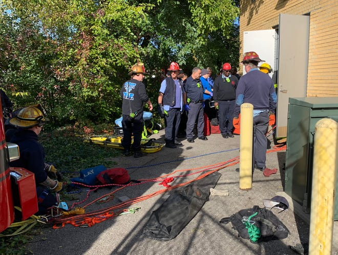 Fire and rescue workers wait to begin extracting the Water and Sewerage Dept. employee from a manhole inside a building. The process required eight ropes and pulleys.