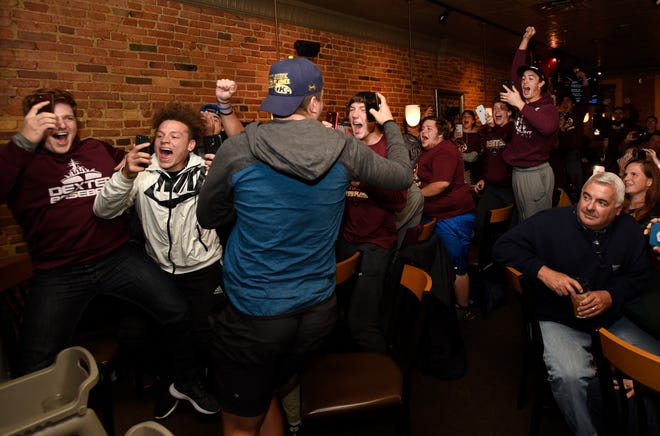 The Dexter football team reacts during a watch show as they find out they'll play South Lyon in the Division 2 playoffs.