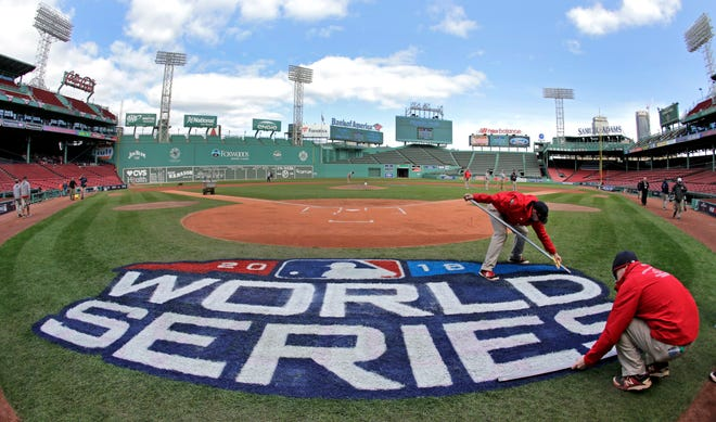 Grounds crew members paint the World Series logo behind home plate at Fenway Park as they prepare for Game 1.