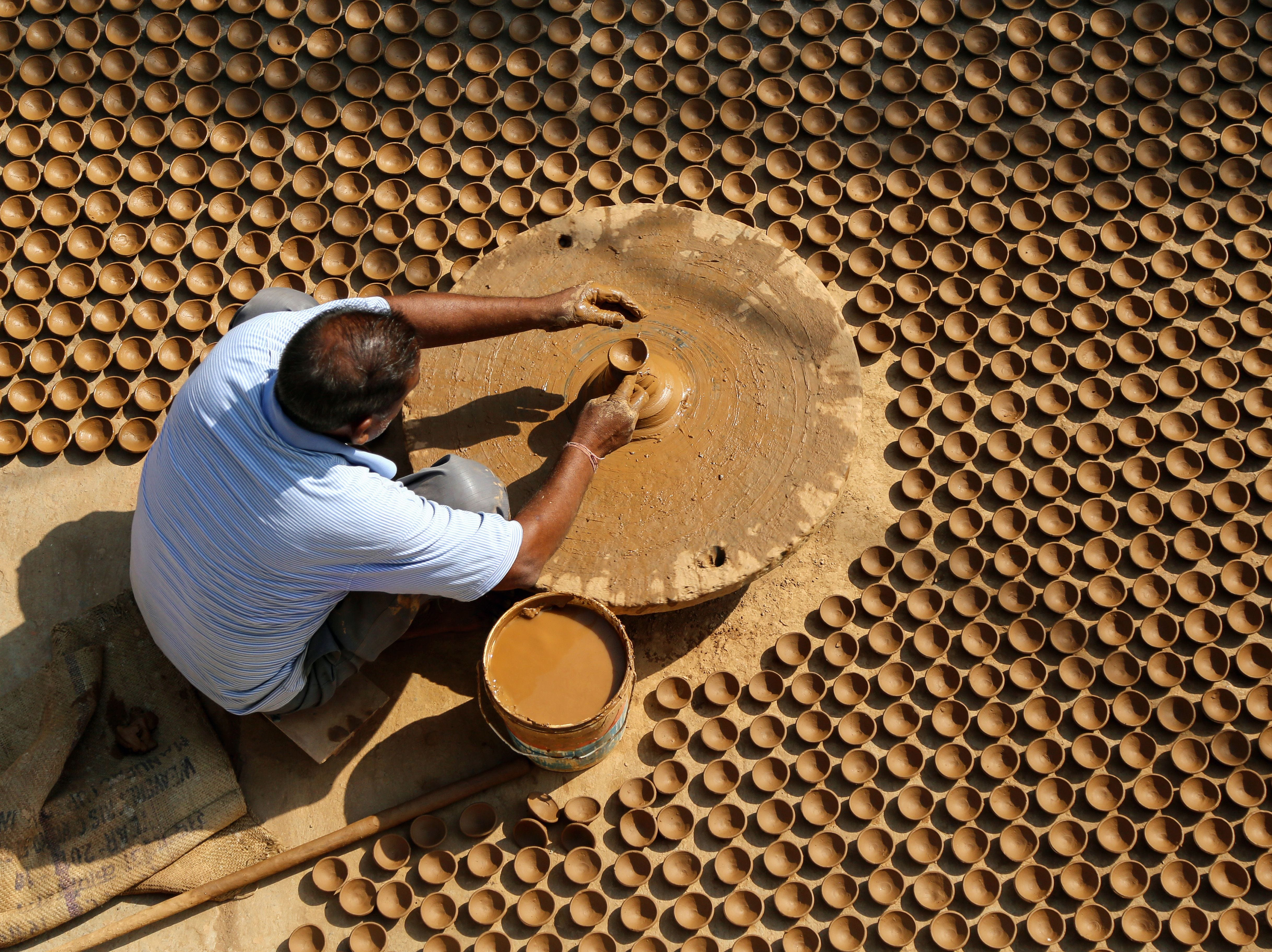 An Indian potter makes diyas (earthen lamps) ahead of the Hindu festival Diwali in Ajmer, in the Indian state of Rajasthan, on October 22, 2018. - The Hindu festival Diwali, or Festival of Lights, will be celebrated in 2018 on November 7.