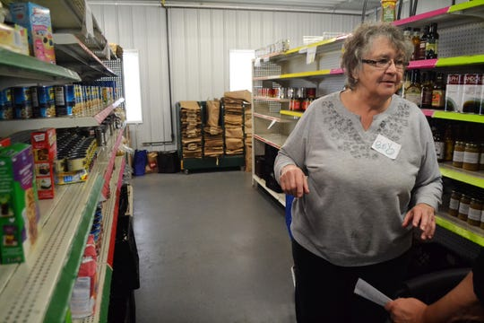 Bev Olson of Lena talks to a client about what kind of food he would like to pickup at Kingdom Come Food Pantry in Oconto Falls on Oct. 9, 2018.