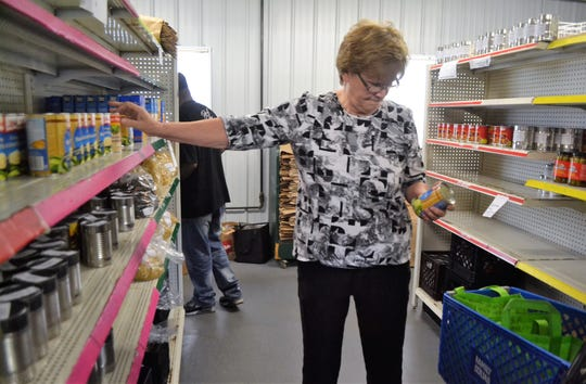 Audrey Ferfecki of Morgan picks up goods for a client in the aisle at Kingdom Come Food Pantry in Oconto Falls on Oct. 9, 2018.