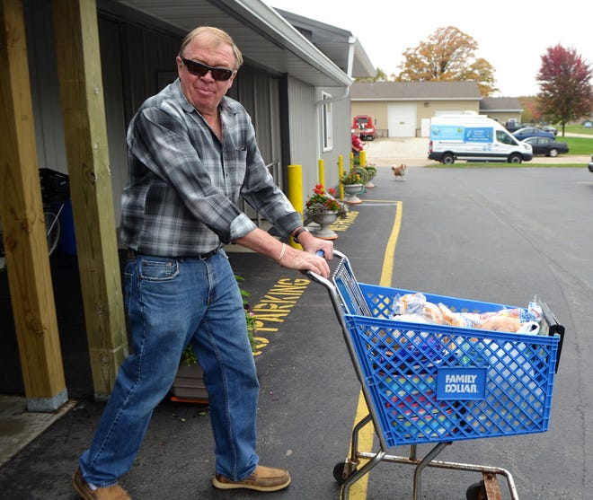 """Steve """"Skunk"""" Krause of Morgan is one of the many volunteers at Kingdom Come Food Pantry in Oconto Falls. Here he rolls a cart of groceries to a client's vehicle for her."""