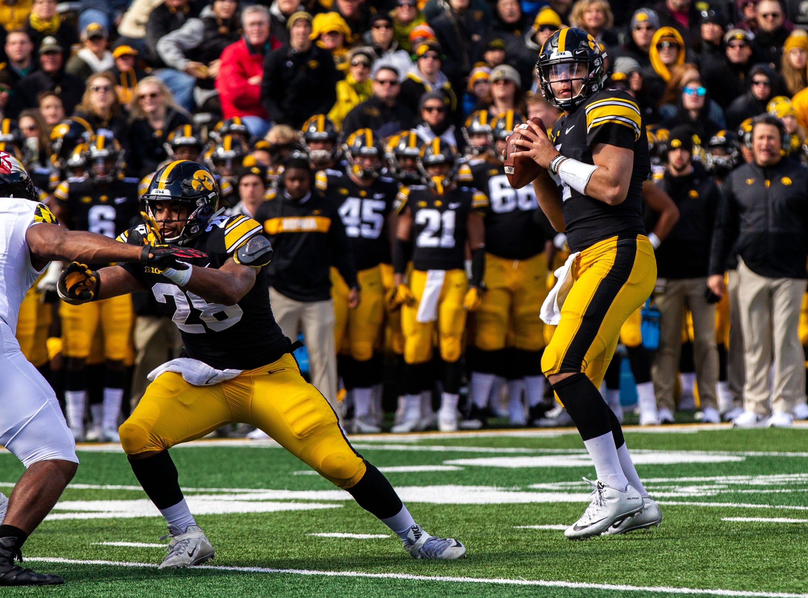Iowa quarterback Nate Stanley (4) looks to pass while Iowa running back Toren Young (28) blocks Maryland linebacker Nnamdi Egbuaba (31) during an NCAA Big Ten conference football game on Saturday, Oct. 20, 2018, at Kinnick Stadium in Iowa City.
