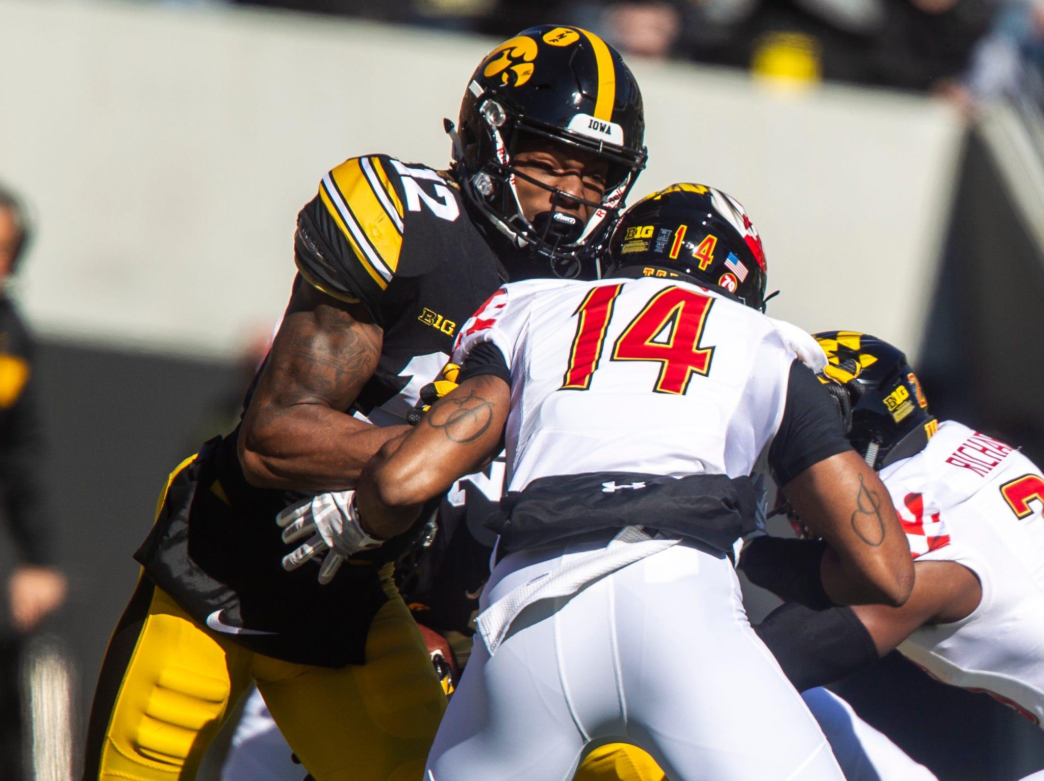 Iowa wide receiver Brandon Smith (12) blocks Maryland defensive back Deon Jones (14) during an NCAA Big Ten conference football game on Saturday, Oct. 20, 2018, at Kinnick Stadium in Iowa City.