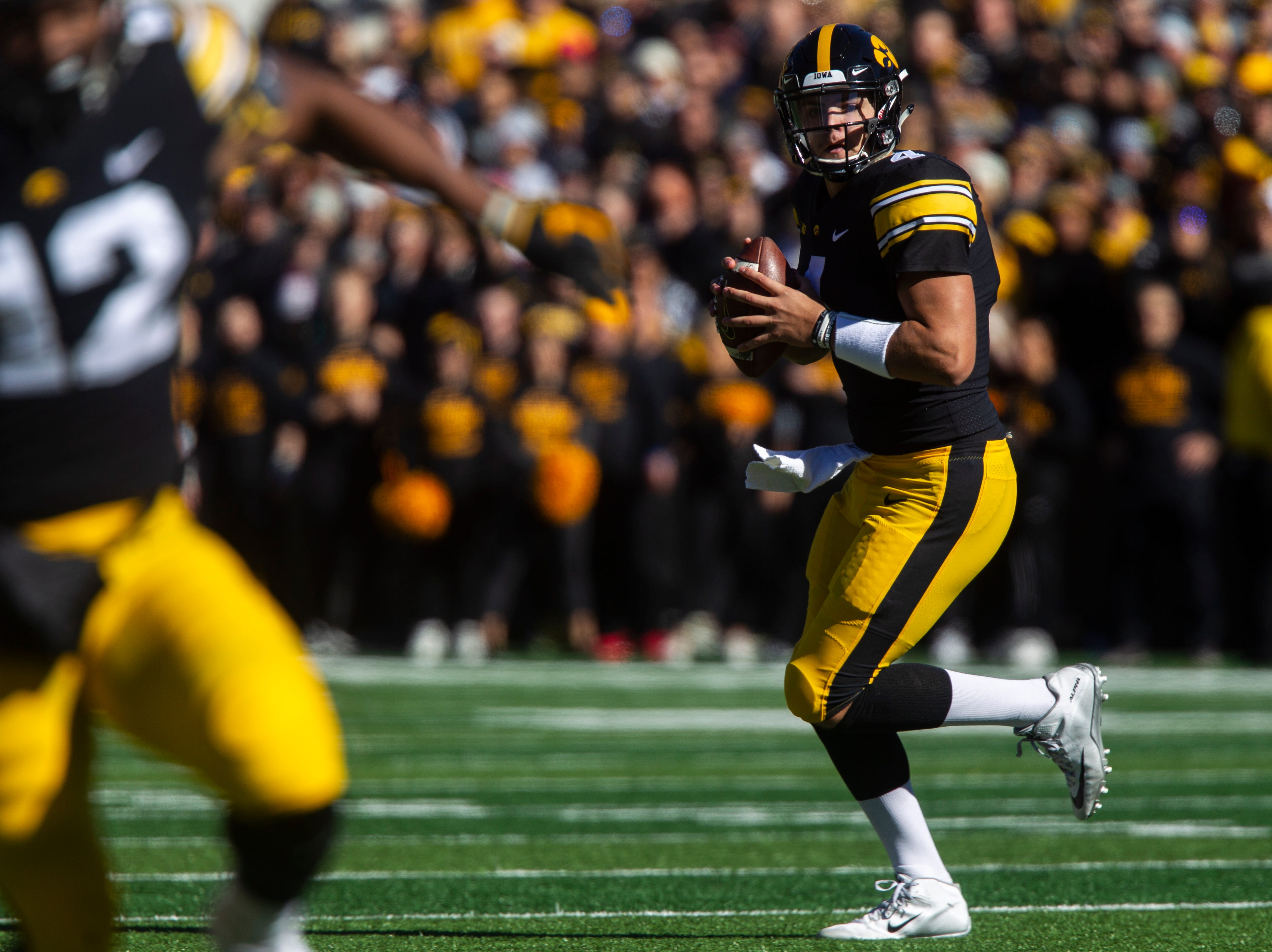 Iowa quarterback Nate Stanley (4) rolls out to pass during an NCAA Big Ten conference football game on Saturday, Oct. 20, 2018, at Kinnick Stadium in Iowa City.