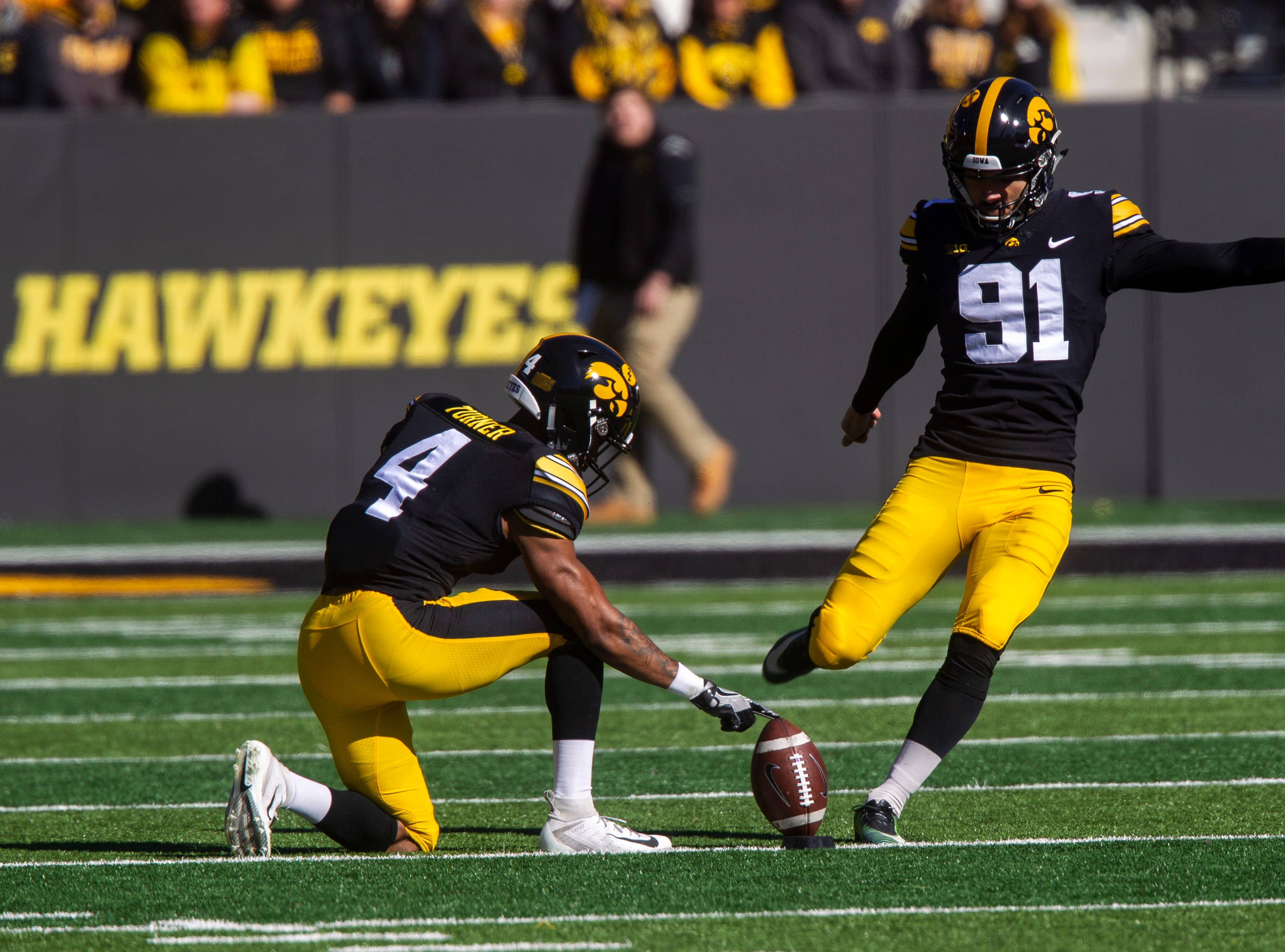 Iowa placekicker Miguel Recinos (91) kicks off while Iowa defensive back Josh Turner (4) holds the ball in the wind during an NCAA Big Ten conference football game on Saturday, Oct. 20, 2018, at Kinnick Stadium in Iowa City.