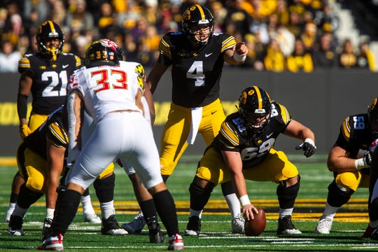 Iowa quarterback Nate Stanley (4) calls out defensive coverage before taking a snap from Iowa center Keegan Render (69).