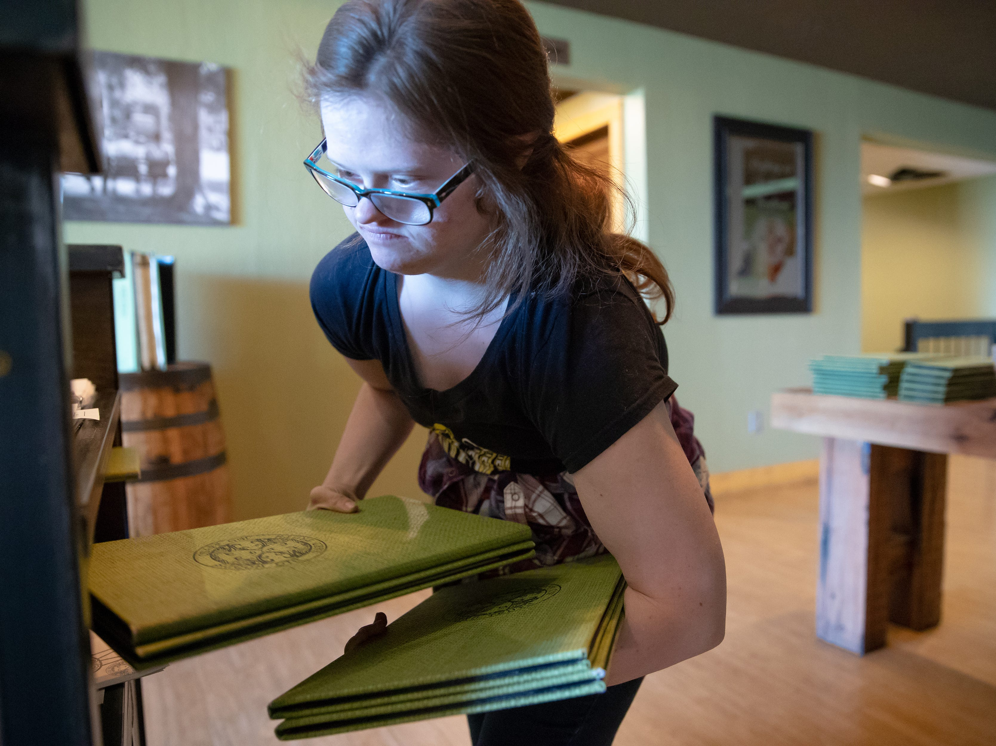 Mickey gathers menus while on shift at Big Woods in Franklin, Ind., on Thursday, Oct. 18, 2018.