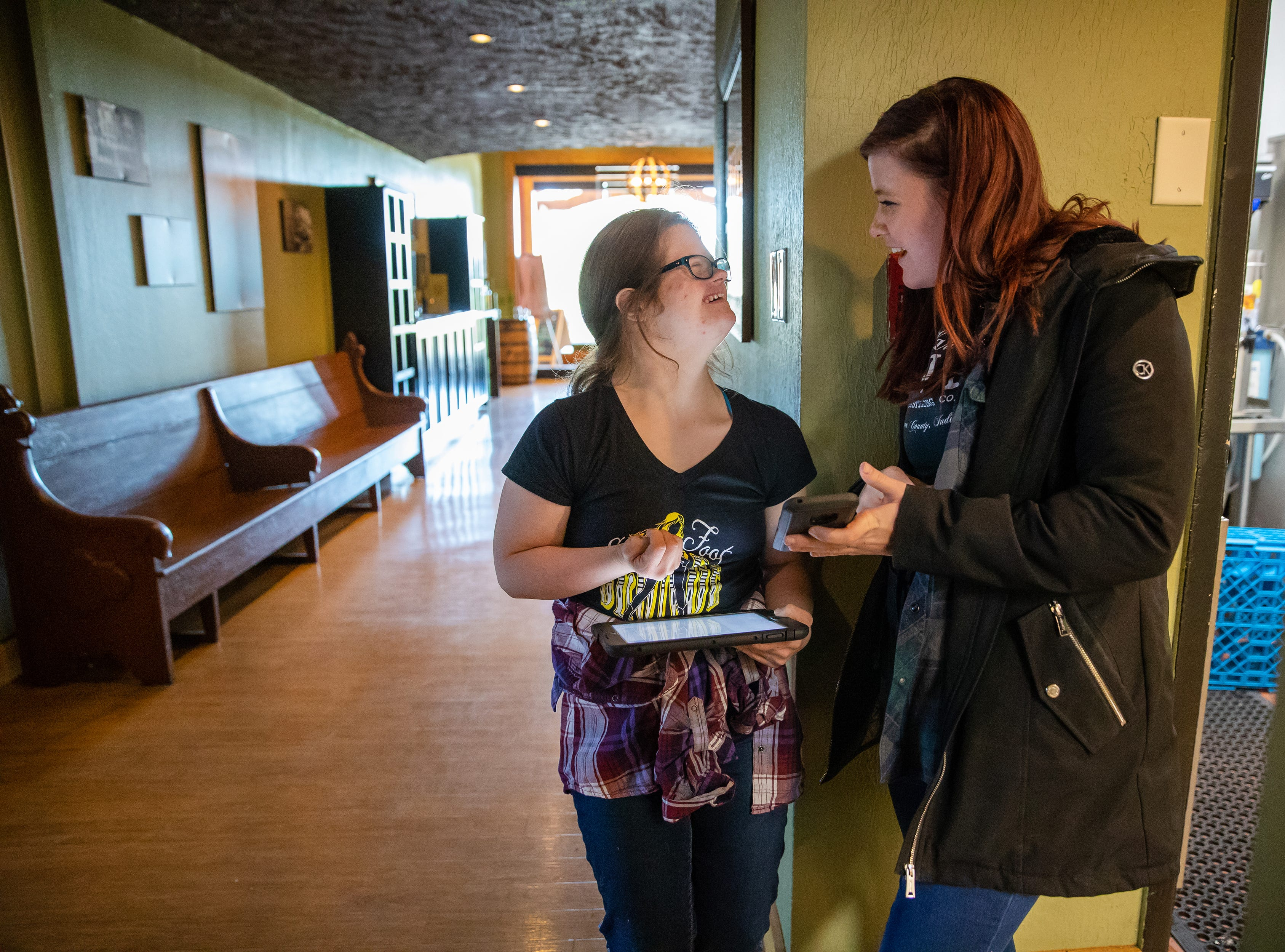 At the beginning of her shift, Mickey Deputy (left) inputs various wait staff into an iPad program at Big Woods in Franklin, Ind., with the help from server Kalyn Guyer on Thursday, Oct. 18, 2018.