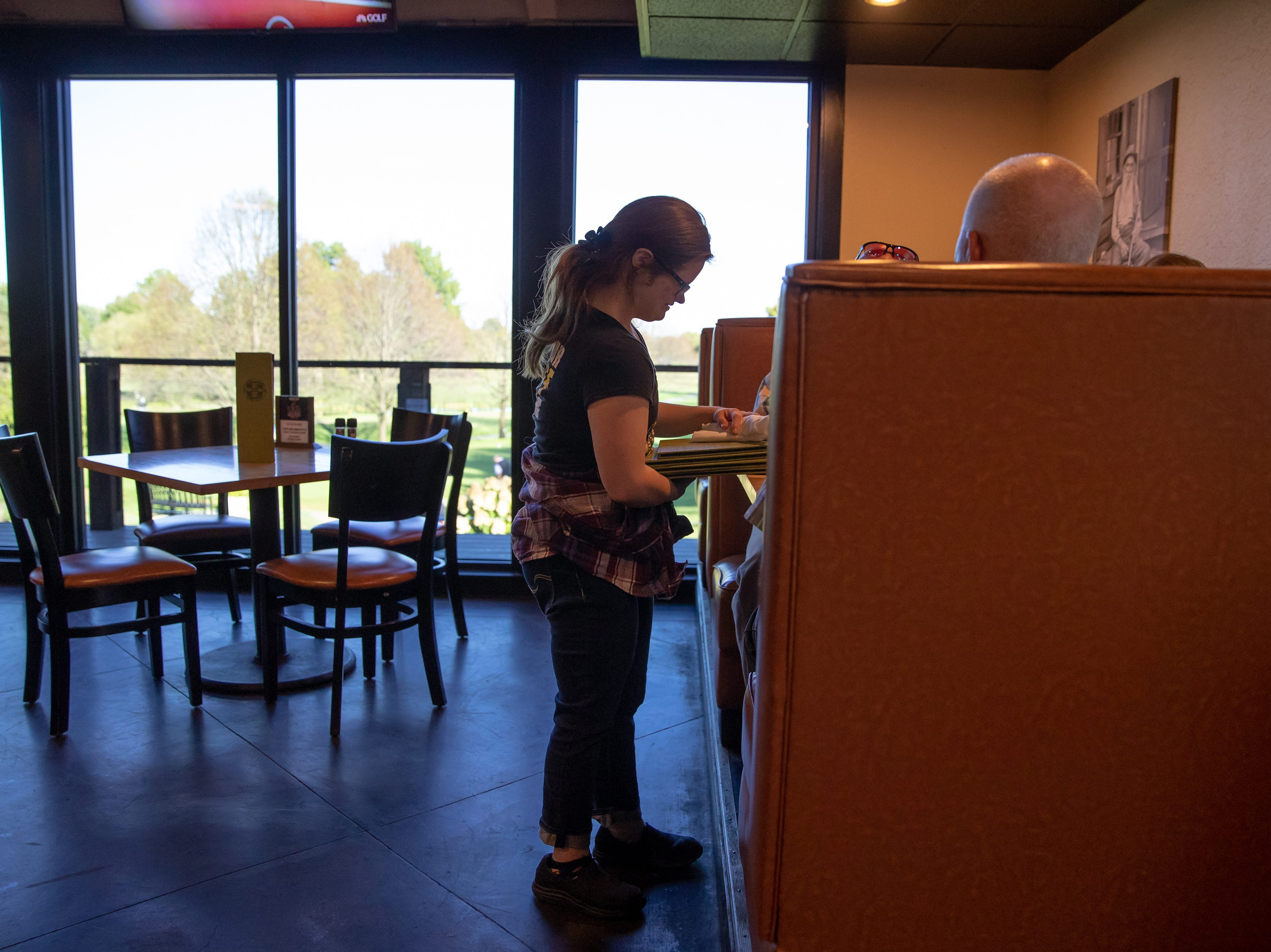 """Mickey seats a family of four while on shift at Big Woods in Franklin, Ind., on Thursday, Oct. 18, 2018. """"Hi, my name is Mickey, like the mouse,"""" she said. """"I'm so glad you're here today with us."""""""