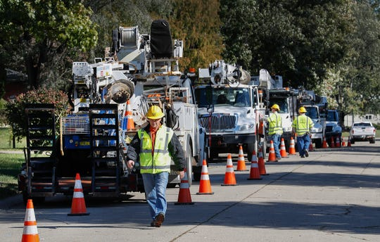 Crews from IPL and contractors from Elliot Electric work together to remove and repair the fallen power lines in the 1900 block of Alwyne Drive on Monday, Oct 22, 2018.