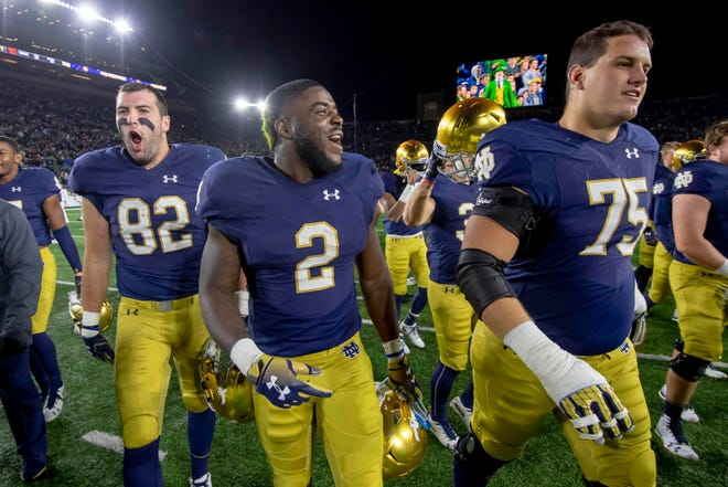 Fighting Irish tight end Nic Weishar (82) , running back Dexter Williams (2) and offensive lineman Josh Lugg (75) celebrate after Notre Dame defeated the Stanford Cardinal.