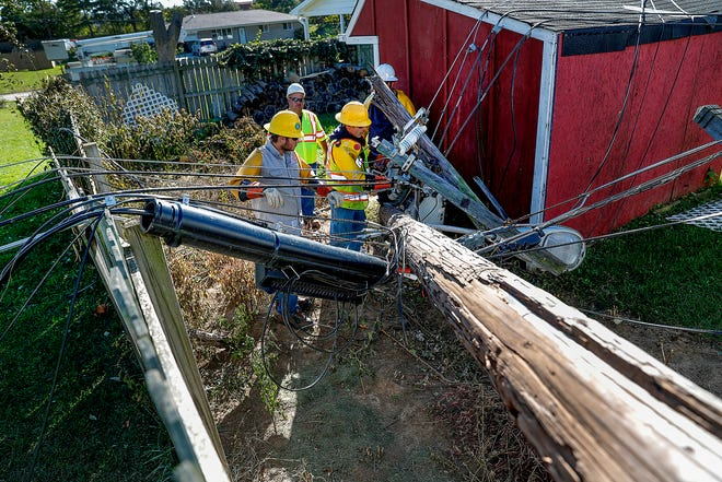 Crews from IPL and contractors from Elliot Electric work together to remove and repair the fallen power lines and poles behind the home at 1902 Alwyne Drive on Monday, Oct 22, 2018.