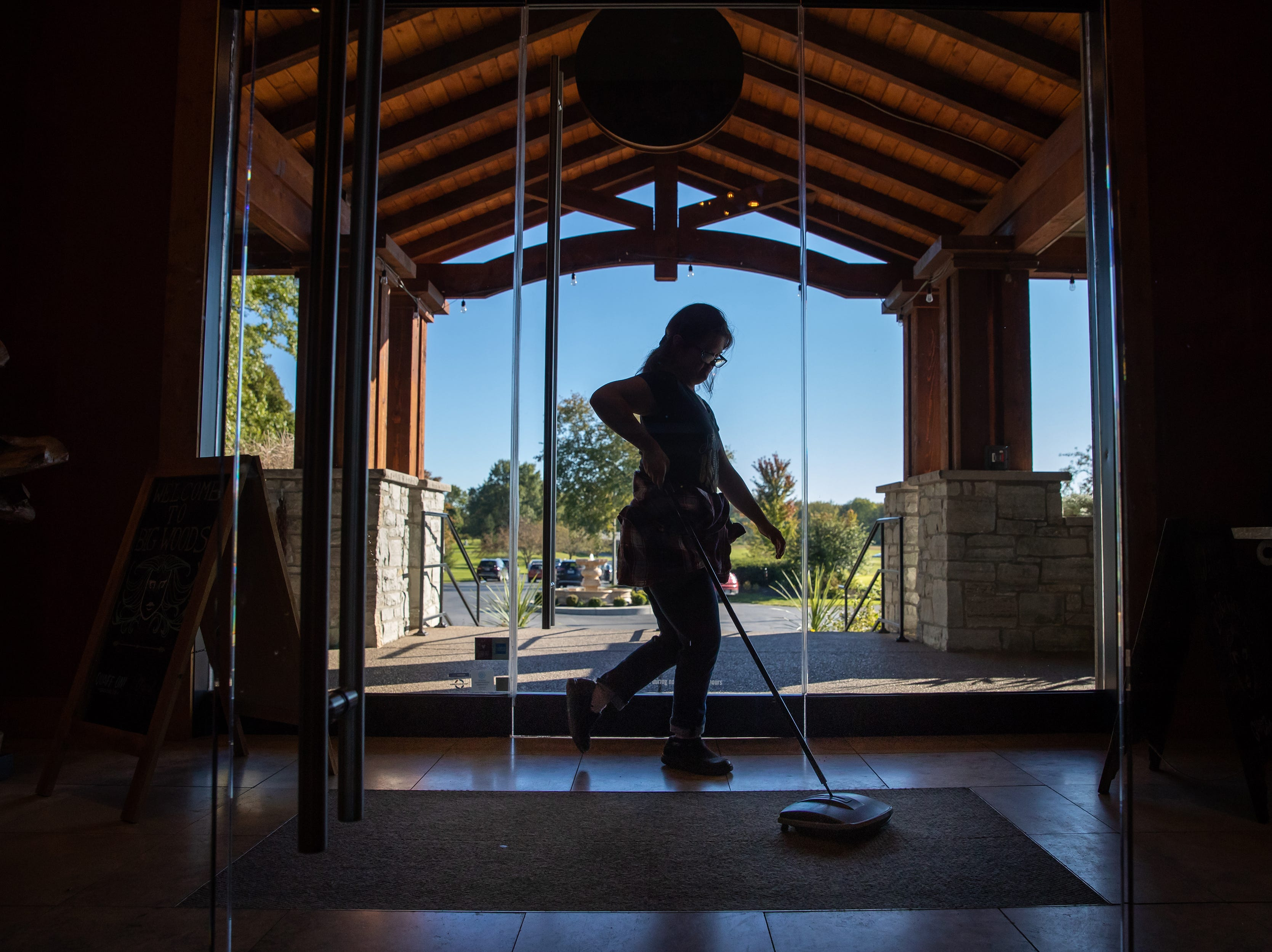 While dancing to music heard at the restaurant, Mickey sweeps the floors while on shift at Big Woods in Franklin, Ind., on Thursday, Oct. 18, 2018.