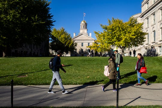 Students walk along Washington Street past the Old Capitol on Monday, Oct. 22, 2018, on the University of Iowa campus in Iowa City.