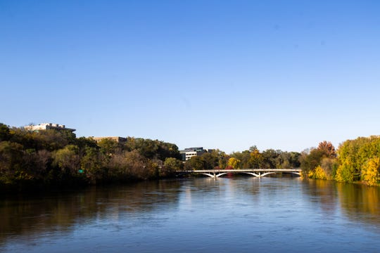 Trees are reflected in the Iowa River on Monday, Oct. 22, 2018, seen from the Burlington Street Bridge in Iowa City.