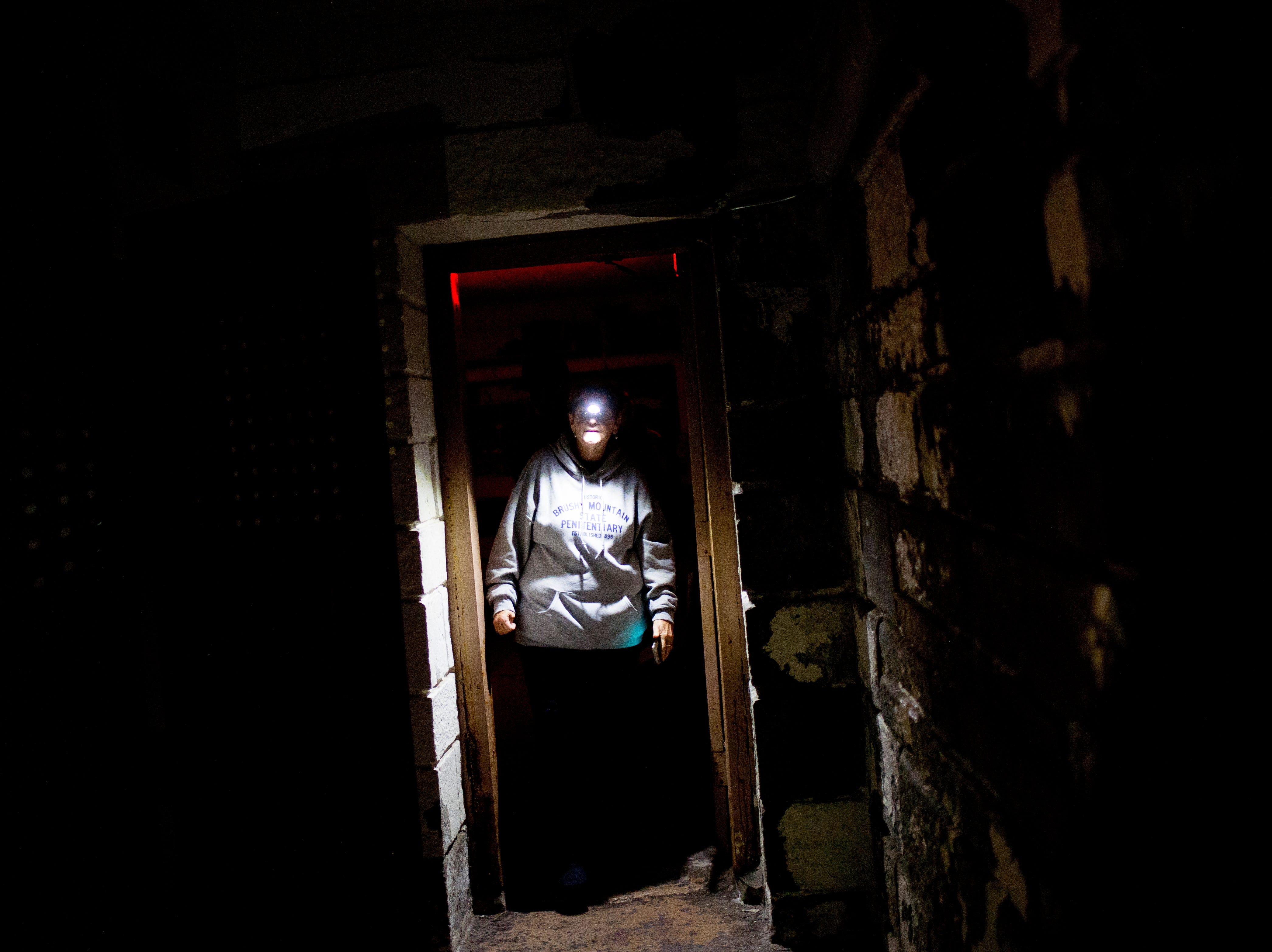 "Debbie Williams, a former correctional officer at the jail for 28 years, walks into ""The Hole"" during a paranormal flashlight tour of Brushy Mountain State Penitentiary in Petros, Tennessee on Tuesday, October 16, 2018."
