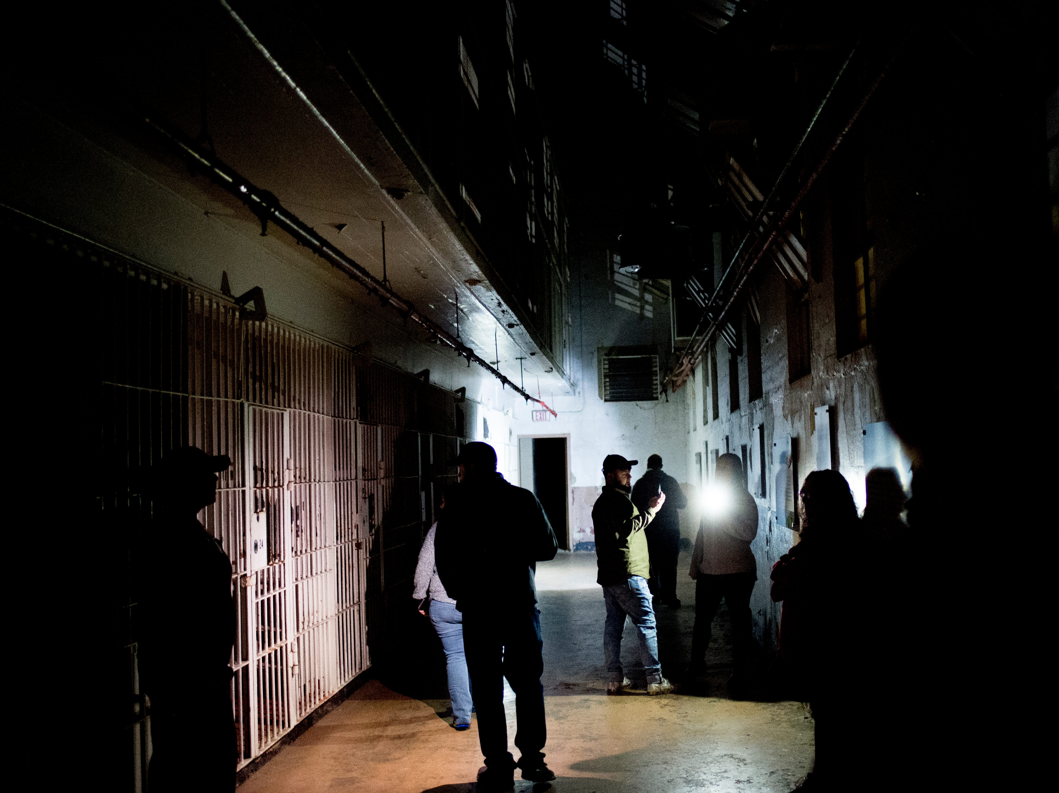 Visitors gather in one of the large cell blocks during a paranormal flashlight tour of Brushy Mountain State Penitentiary in Petros, Tennessee on Tuesday, October 16, 2018.