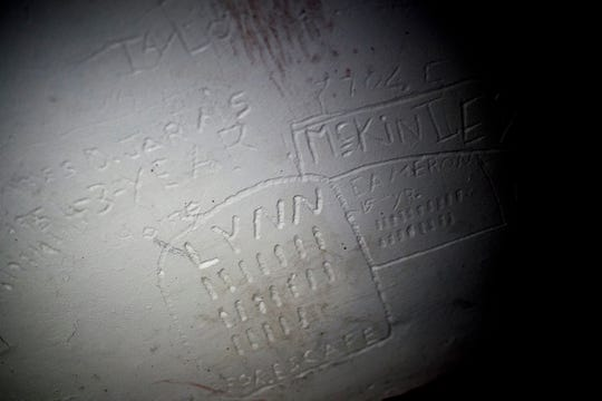 """Etchings in the wall by inmates held in the solitary confinement cells, known as """"The Hole,"""" can still be seen today during a paranormal flashlight tour of Brushy Mountain State Penitentiary in Petros, Tennessee on Tuesday, October 16, 2018."""