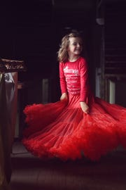 Mallory Bertrand's daughter, Lily, models her mother's red crinoline, a flea market find.