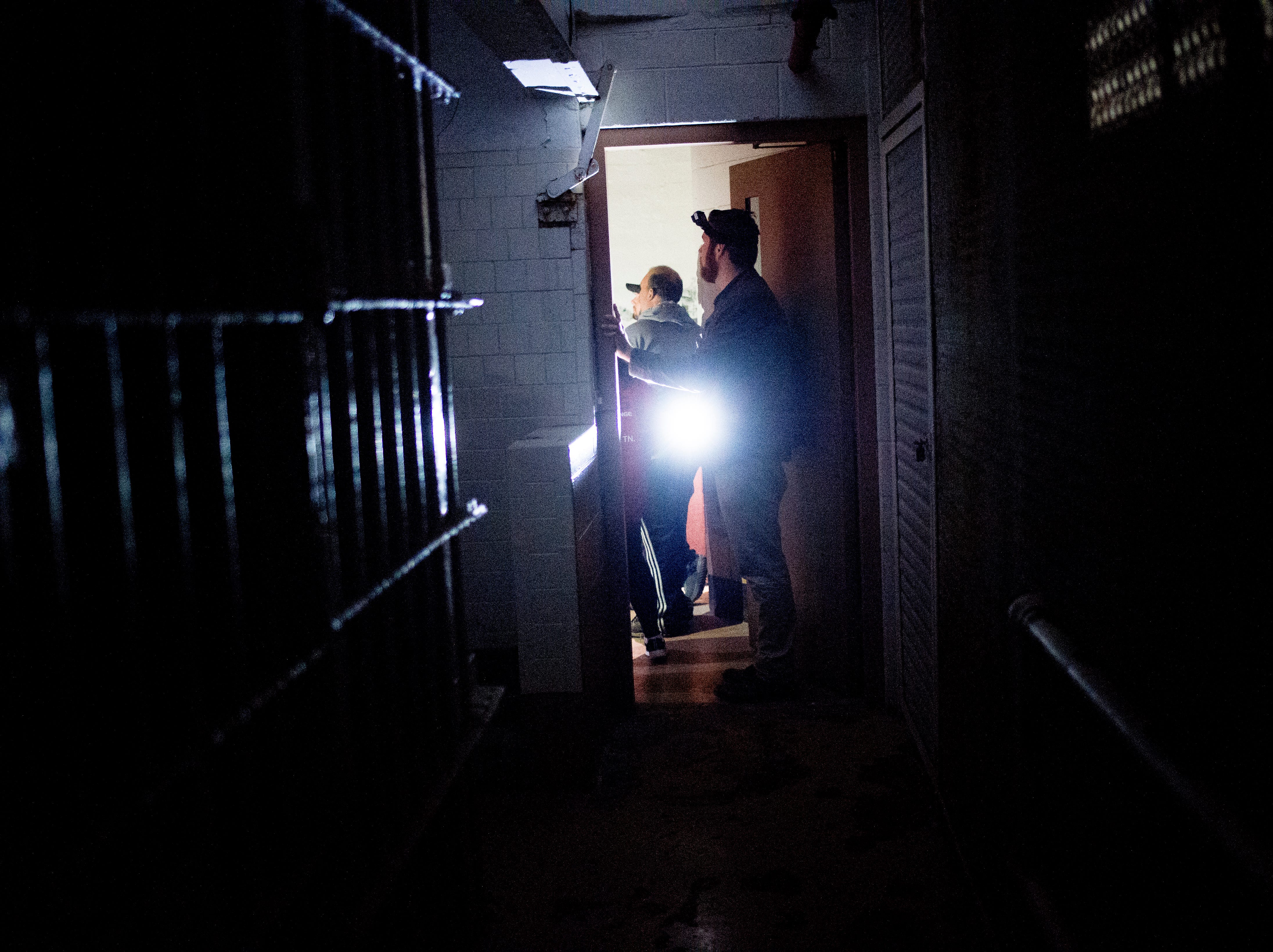News Sentinel reporter Ryan Wilusz walks through a cell block during a paranormal flashlight tour of Brushy Mountain State Penitentiary in Petros, Tennessee on Tuesday, October 16, 2018.