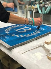A wooden sign is painted at one of AR Workshop's classes. The DIY crafting studio franchise will open a location in Knoxville on Thursday, Oct. 25.