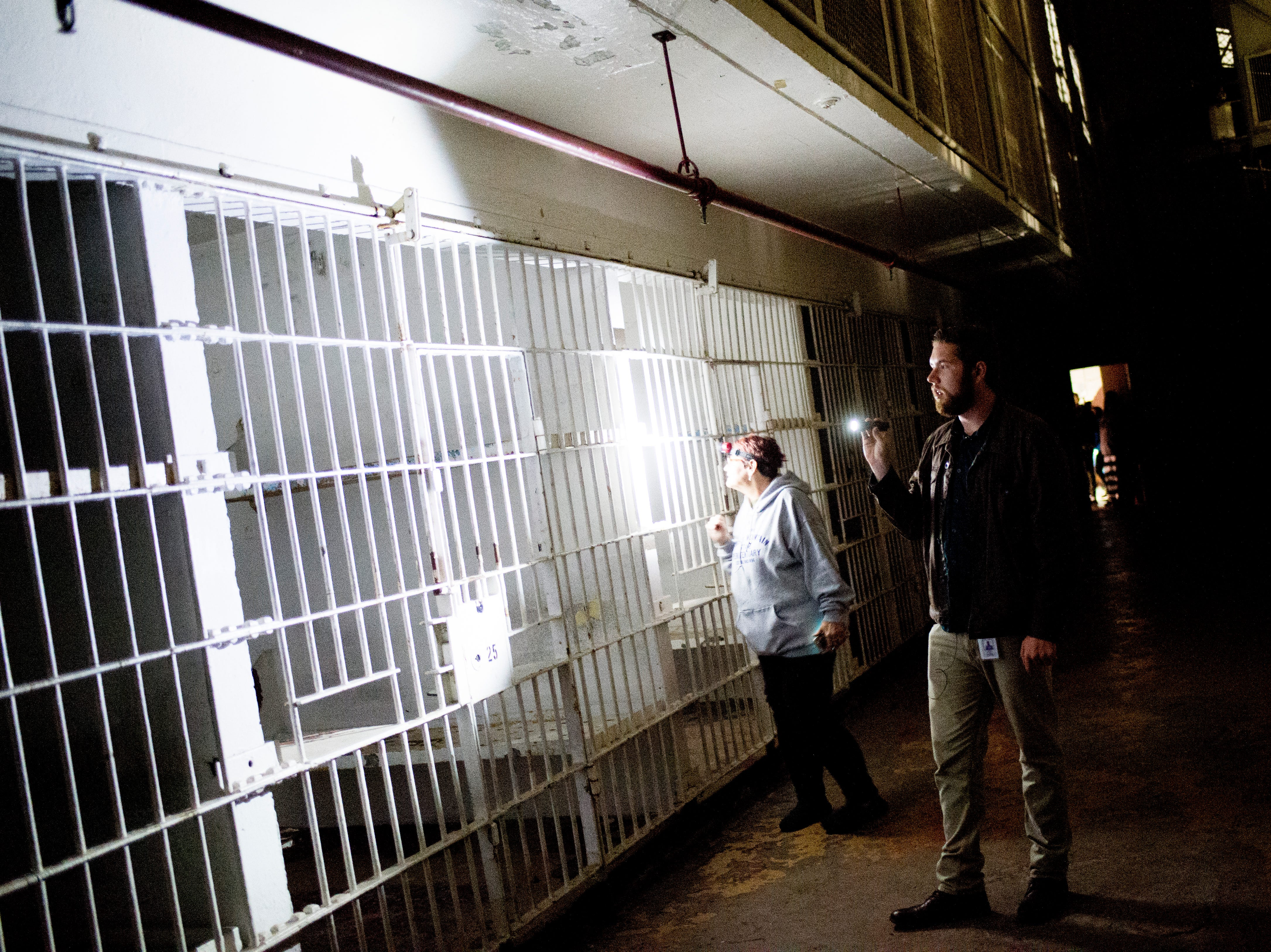 Ryan Wilusz and tour guide Debbie Williams, who worked at the prison for 28 years, look at jail cells during a paranormal flashlight tour of Brushy Mountain State Penitentiary in Petros, Tennessee on Tuesday, October 16, 2018.