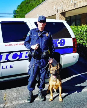 Officer Ryan Ayers stands with his new K-9 partner Jack, a 2-year-old Belgian Malinois.
