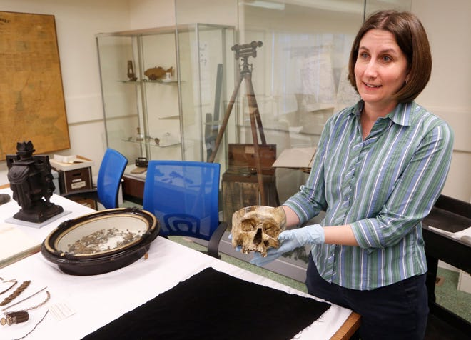 Kelly Lippie displays the skull of David Stocking Monday, October 22, 2018, at the Tippecanoe County Historical Association, 1001 South Street in Lafayette. Stocking was executed by hanging on the Tippecanoe County Courthouse  lawn in 1856 for the crimes of robbery, arson and murder. Lippie is curator of collections at the TCHA.