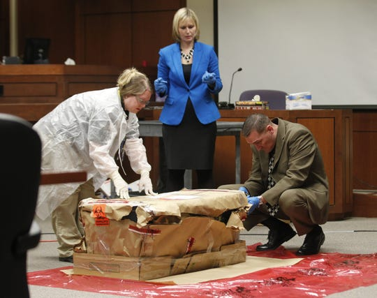 Louisville Metro Police Evidence Tech Jessica Silver (left), Assistant Commonwealth's attorney Ryane Conroy and then-Louisville Metro Police Detective Jon Lesher examine the box that held the body of a murder victim during a 2013 trial at the Jefferson County Judicial Center.