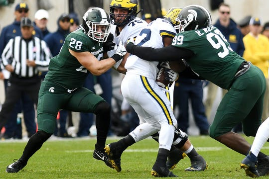 Michigan State's Raequan Williams, right, tackles Michigan's Karan Higdon as MSU's Jon Reschke closes in during the first quarter on Saturday, Oct. 20, 2018, in East Lansing.