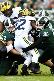 Michigan State's Mike Panasiuk, left, and Panasiuk tackle Michigan's Karan Higdon during the first quarter on Saturday, Oct. 20, 2018, in East Lansing.