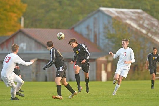 Lexington's Teddy Togliatti heads the ball Monday evening during the Division II Soccer Tournament at Lexington High School against Huron.