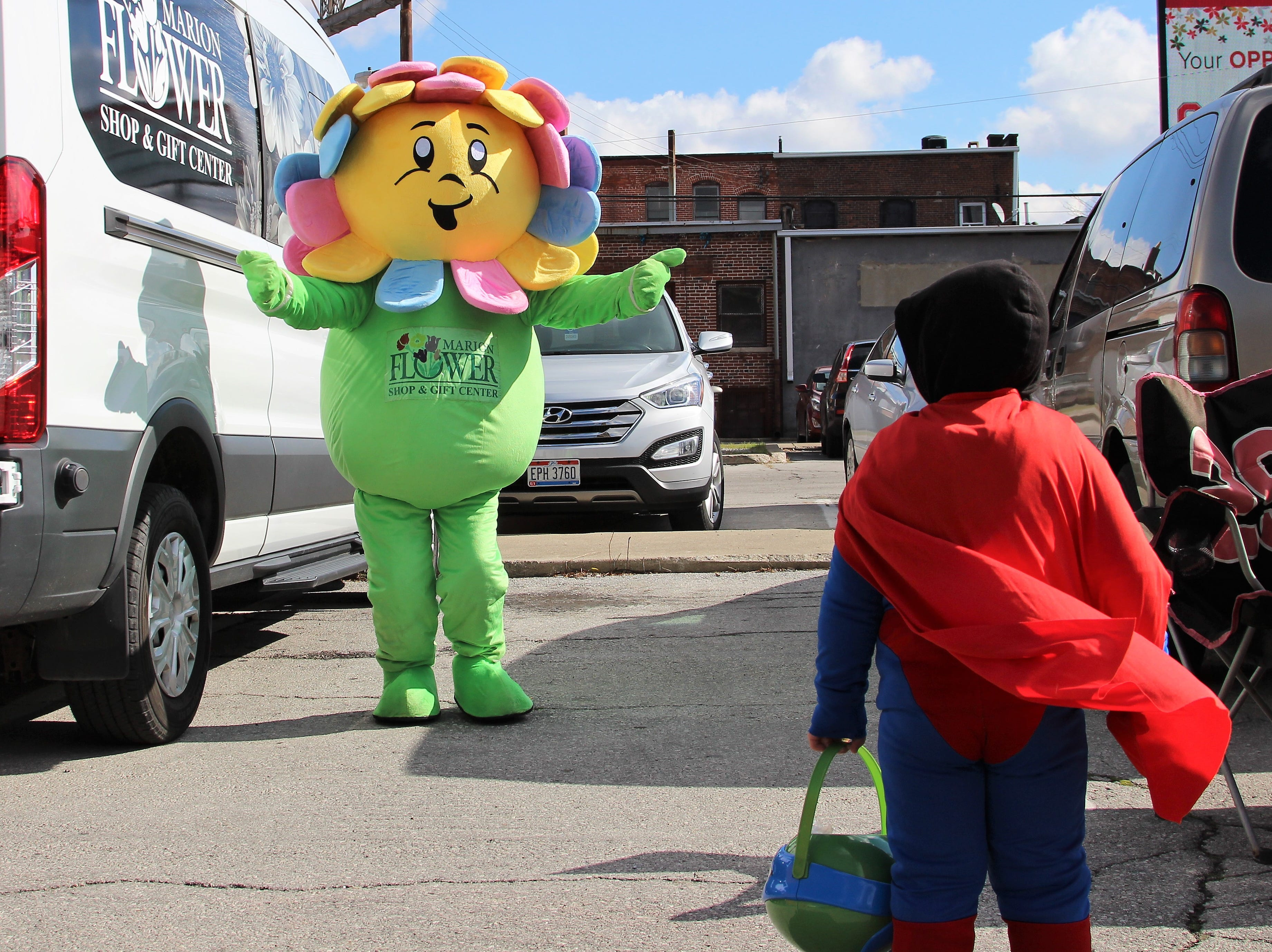 A young boy dressed as superman inches for a hug with the mascot of the Marion Flower Shop on Saturday. He was there to collect candy as downtown offices and businesses participated in the second annual Monster March.