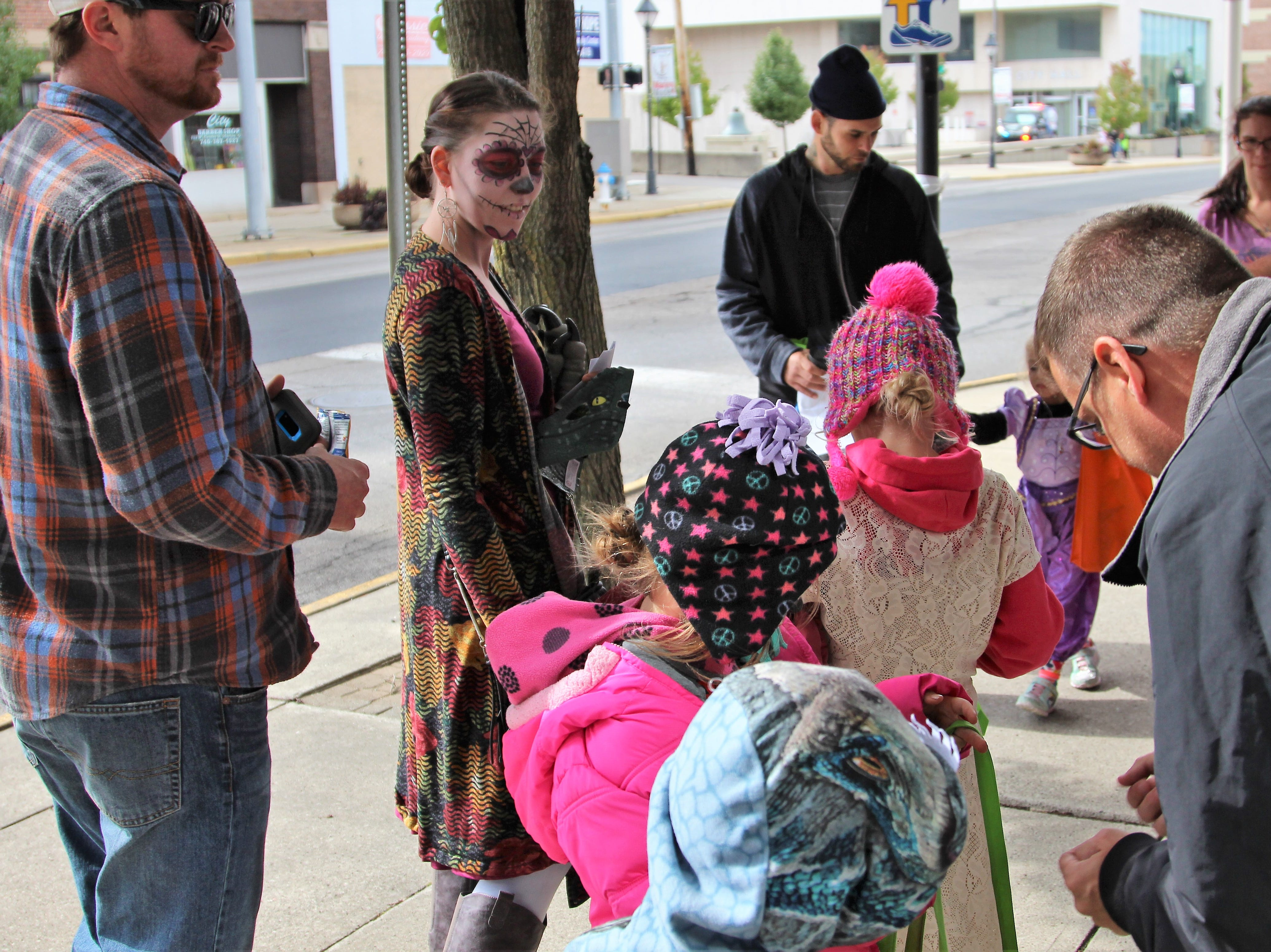 Marion County Prosecutor candidate Jeff Ratliff passes out candy outside his law office on West Center Street. Young residents adorned in Halloween costumes spent the early part of Saturday afternoon collecting candy from downtown businesses, governmental offices and first responders.