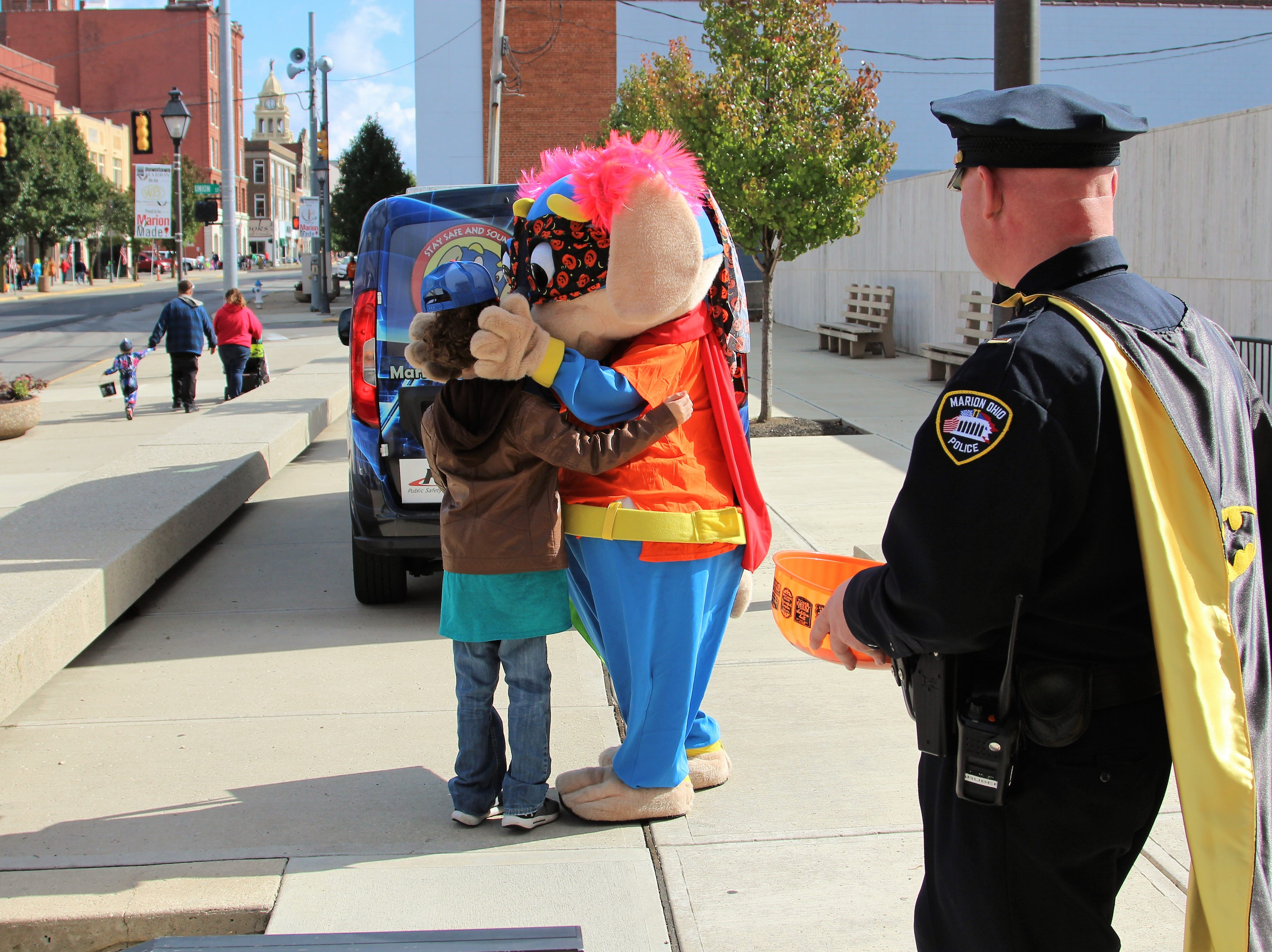 "Marion Police Lt. B.J. Gruber, also known as ""Bat Cop,"" watches as Safety Pup hugs a young trick-or-treater on Saturday."