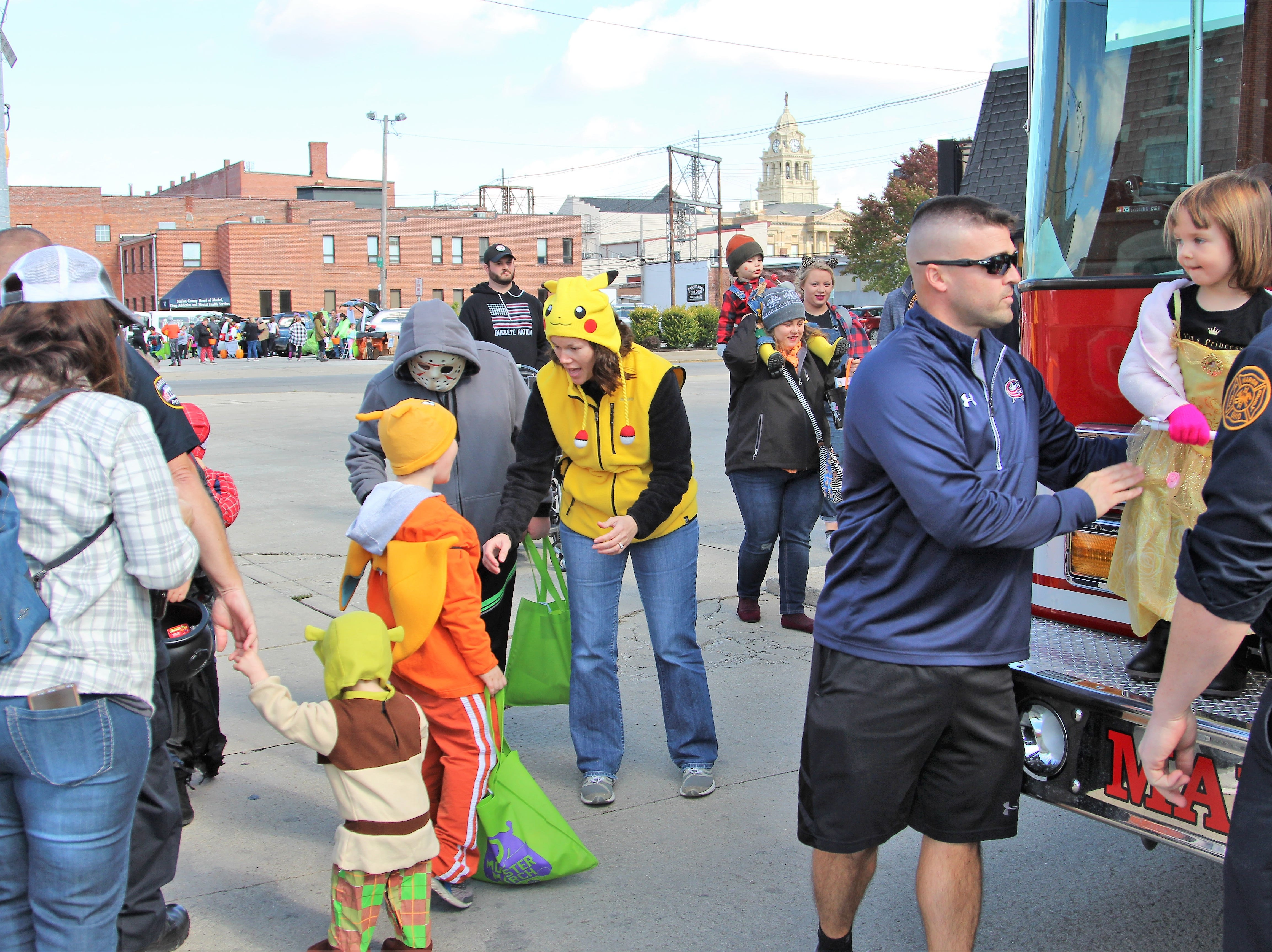 Marion City Firefighters stand outside the department's Station 1 on South Prospect Street as costumed residents searched for candy on Saturday.