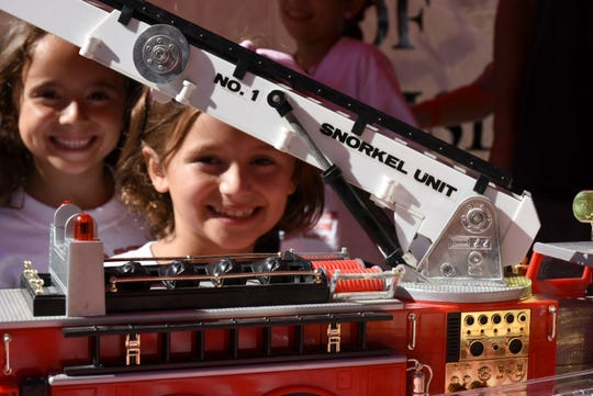 Angelina Oliver, 8, hangs out with a friend and a firetruck at her dad's booth. The Marco Island Fire-Rescue Foundation held their sixth annal Jerry Adams Chili Cookoff Saturday at the Esplanade, raising funds to help fire department families impacted by Hurricane Michael.