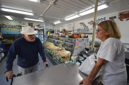 Customer Kick Bolin of Naples came to get his first stone crab claws of the season from Pat Kirk at Kirk Fish Co. in Goodland on Saturday. The local stone crab season is off to a slow start for area fishermen, with longtime observers saying bad weather is needed for a good crab harvest.