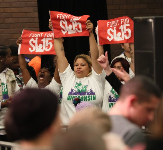 Supporters of the $15 dollar an hour minimum wage hold up flags at a campaign rally at UW-Milwaukee Oct. 22, 2018.