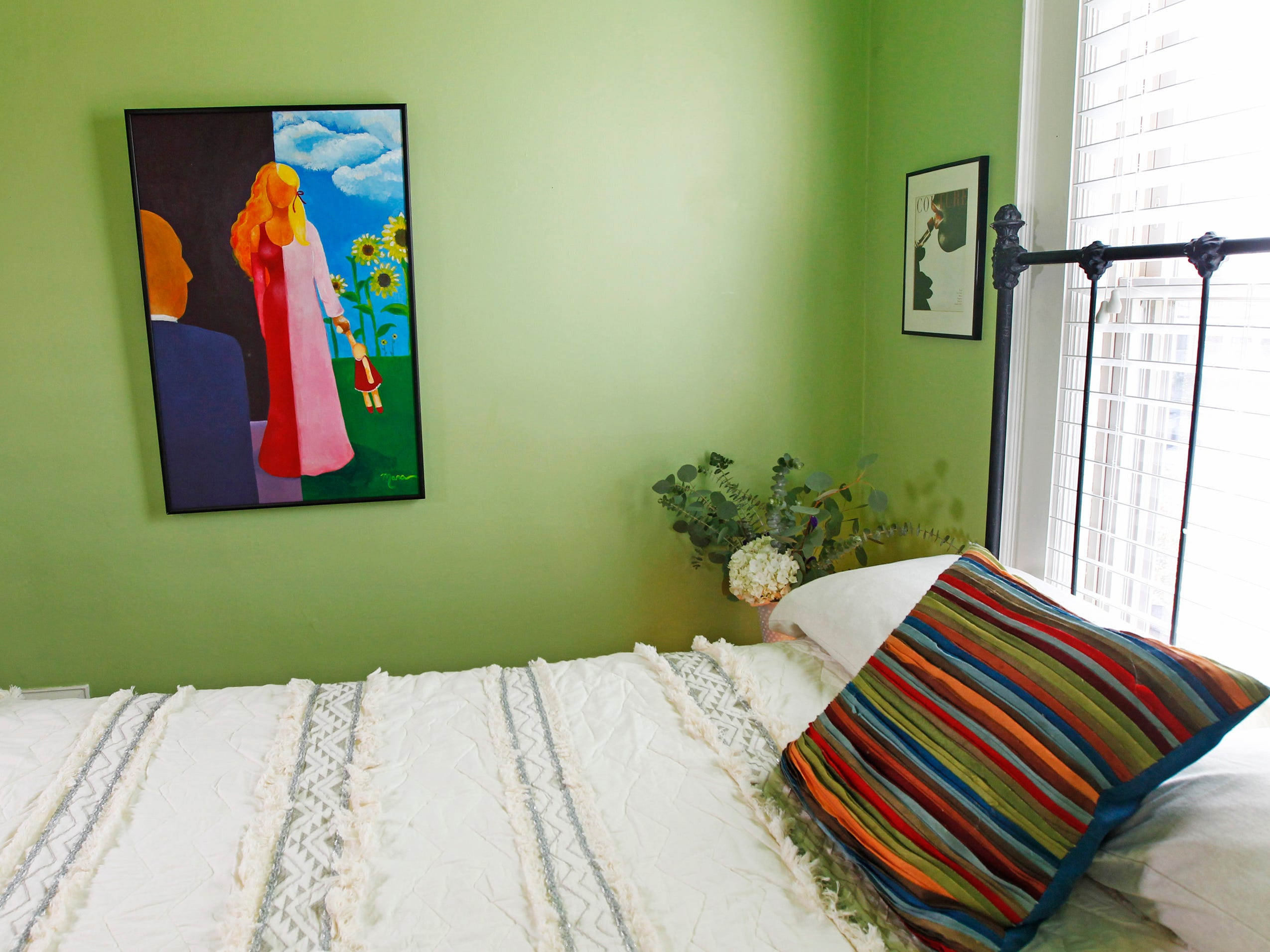 The guest bedroom has colorful walls that provide a bright background for the artwork of homeowner Mara Duckens.